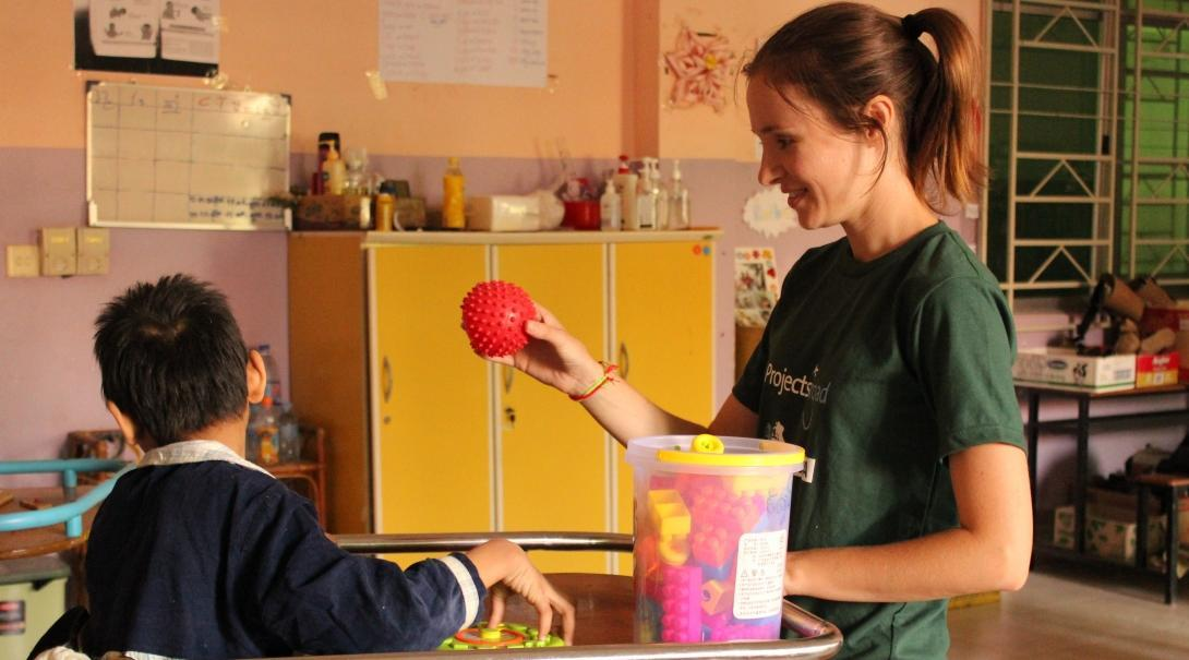 An occupational therapy internship student in Cambodia is pictured playing and engaging with a young child during her work experience with Projects Abroad.